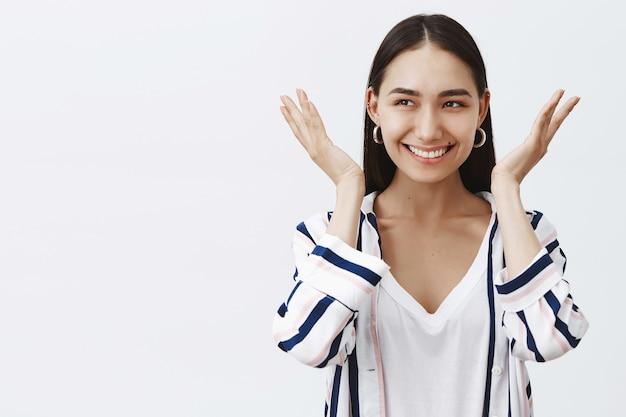 Vrouw tevreden gevoel na het bijwonen van schoonheidstherapeut. portret van zelfverzekerde, zorgeloze europese vrouw met moedervlek onder de lip, breed glimlachend en gezicht openend, breed glimlachend, geamuseerd