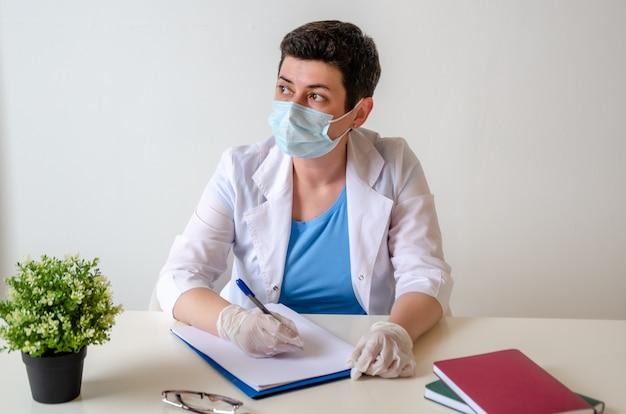 Vrouw therapeut met een beschermend masker, zittend aan de tafel, kijkend uit het raam, mediteren. bij de dokter.