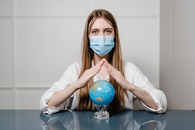 Vrouw thuis achter bureau dat masker draagt en aardebol houdt
