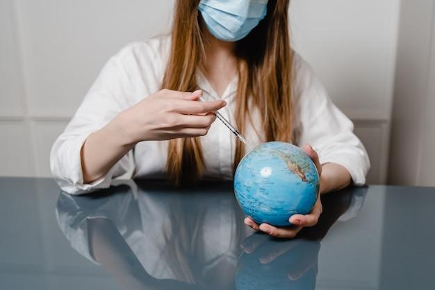Vrouw thuis achter bureau dat masker draagt en aardebol met spuit injecteert