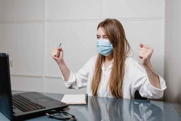 Vrouw thuis bureau met laptop die masker draagt en fuck u gebaar toont
