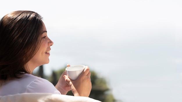Vrouw thuis genieten van kopje koffie