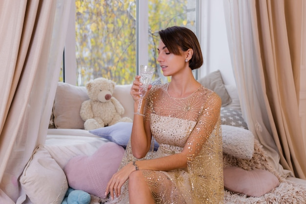 Vrouw thuis gezellige kamer dragen kerst glanzende avondjurk, met glas champagne