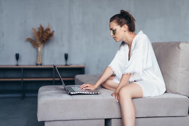 Vrouw thuis in een nachthemd met een tijdschrift, een glas en vlekken op haar gezicht.