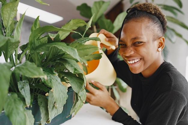 Vrouw thuis. meisje in een zwarte trui. afrikaanse vrouw die de plant water geeft. persoon met bloempot.