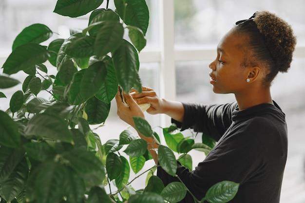 Vrouw thuis. meisje in een zwarte trui. afrikaanse vrouw gebruikt de doek. persoon met bloempot.