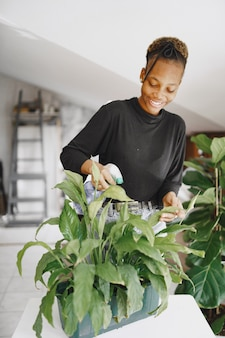 Vrouw thuis. meisje in een zwarte trui. afrikaanse vrouw op kantoor. persoon met bloempot.