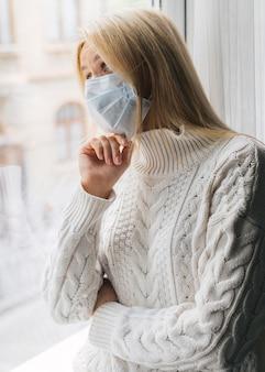 Vrouw thuis met medisch masker tijdens de pandemie die door het raam kijkt
