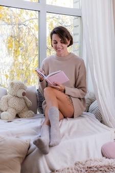Vrouw thuis met notitieboekje zitten op vensterbank in comfortabele trui en warme wollen sokken, koud buiten raam buiten