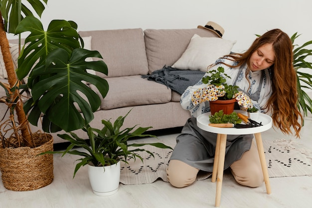 Vrouw thuis met pot van plant en tuinieren tool