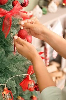 Vrouw thuis mooie kerstboom versieren, close-up