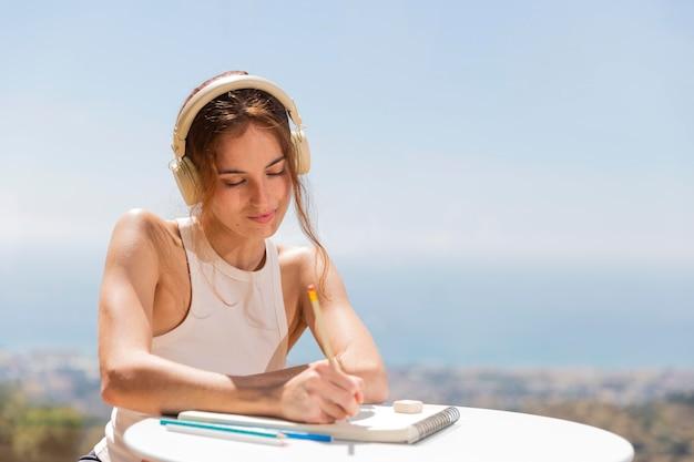 Vrouw thuis muziek luisteren en tekenen