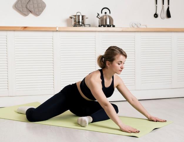 Vrouw thuis oefenen op mat