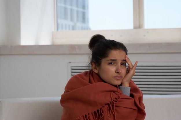 Vrouw thuis op de bank verstopt met een deken koude ontevredenheidsbehandeling