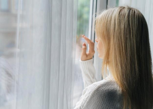 Vrouw thuis tijdens de pandemie die door het raam kijkt