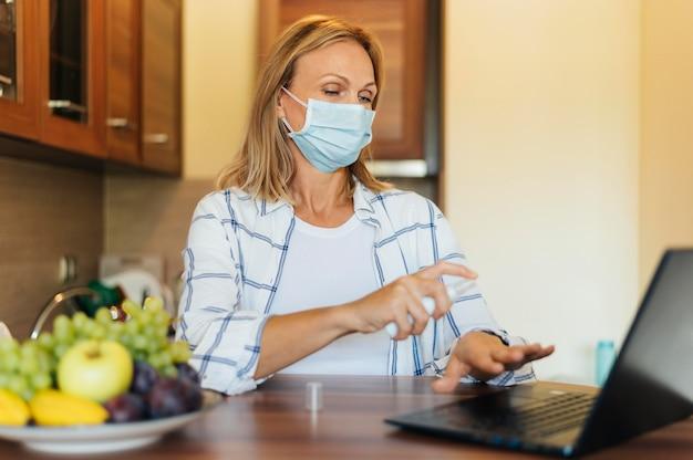 Vrouw thuis tijdens quarantaine met medisch masker en laptop