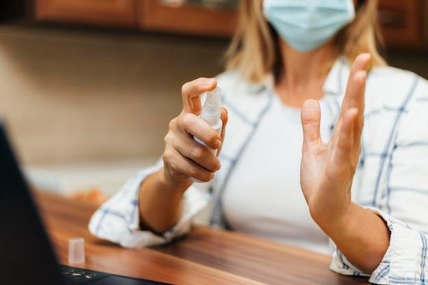 Vrouw thuis tijdens quarantaine sproeien handdesinfecterend middel op handen