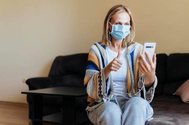 Vrouw thuis tijdens zelfisolatie met medisch masker en smartphone
