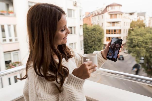 Vrouw thuis video bellen met vrienden in quarantaine met koffie