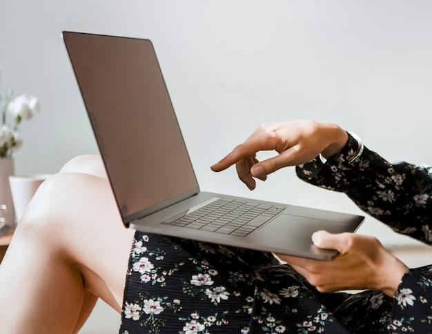 Vrouw thuis wijzend op een laptopscherm