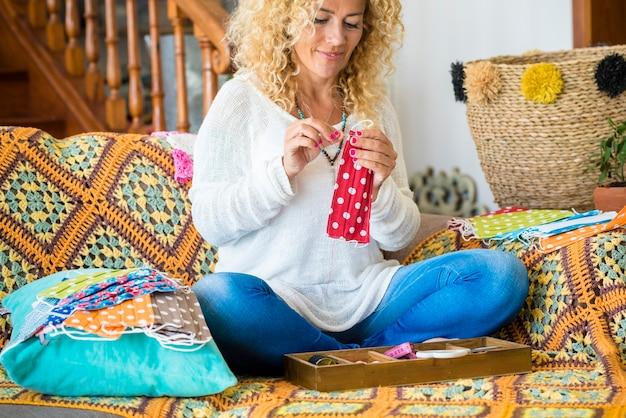 Vrouw thuis zittend op de bank doet medische bescherming wegwerp tegen coronavirus covid