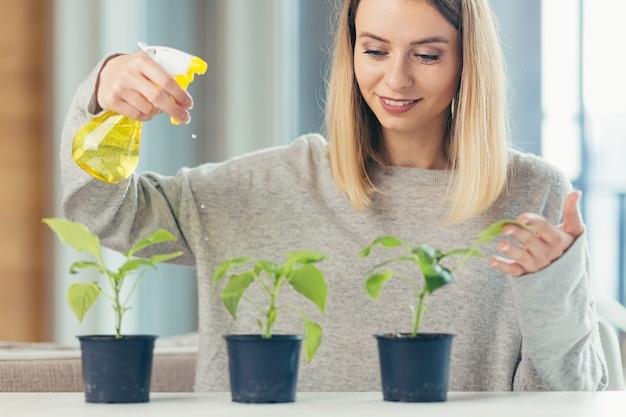 Vrouw thuis zorgt voor bloempotten schenkt bloemen zittend aan tafel