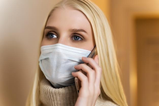 Vrouw tiener jonge vrouw die een gezichtsmasker draagt tijdens covid-19 coronavirus pandemie buitenshuis praten over haar smartphone