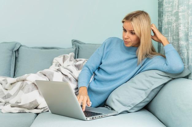 Vrouw tijdens de pandemie die aan laptop thuis werkt