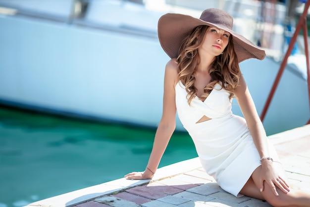 Vrouw tijdens de zomervakantie met een hoed op haar hoofd slenteren in een jachthaven