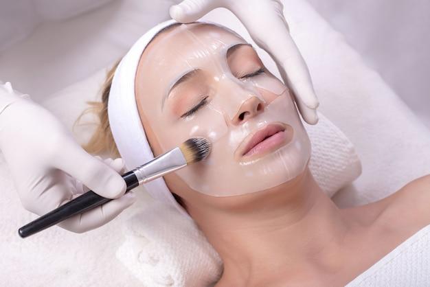Vrouw tijdens een schoonheidshuidmaskerbehandeling op haar gezicht met een borstel
