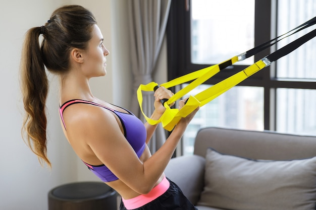 Vrouw tijdens haar training thuis met ophangriemen