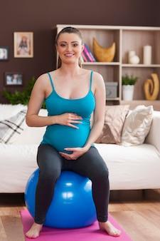 Vrouw tijdens pilates tijdens zwangerschap thuis