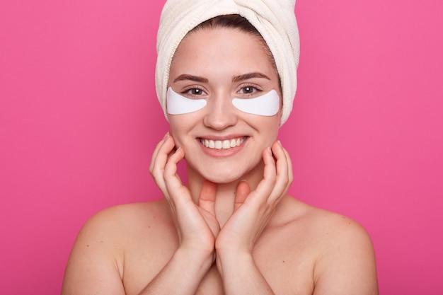Vrouw tijdens spa-procedure. aantrekkelijke dame met een gezonde huid poseren met patches onder de ogen en witte handdoek op het hoofd
