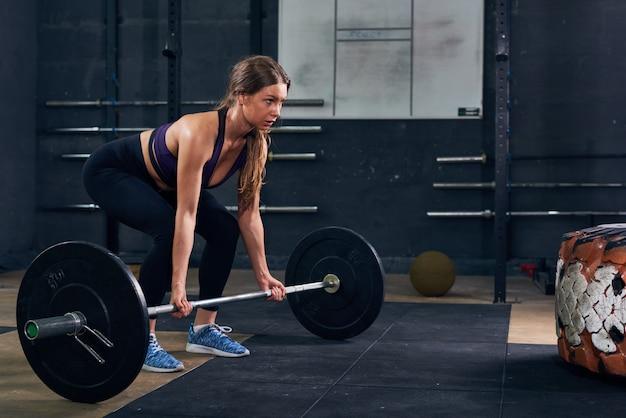 Vrouw tillen van zware barbell in crossfit gym