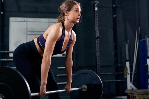 Vrouw tillen van zware barbell