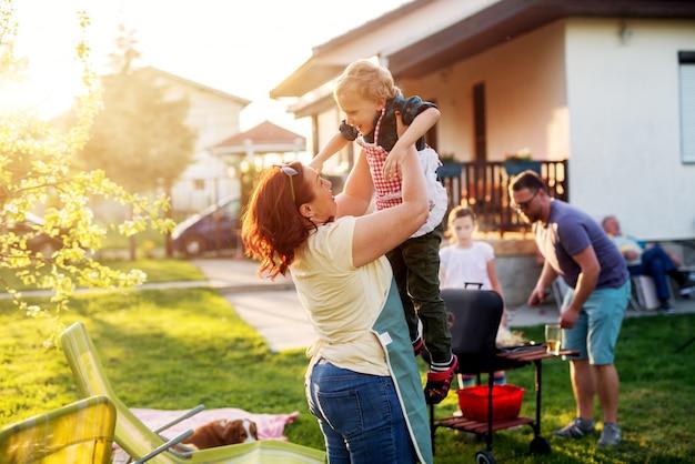 Vrouw tilt haar prachtige en vrolijke peuterjongen hoog op terwijl de rest van de familie aan het grillen is.