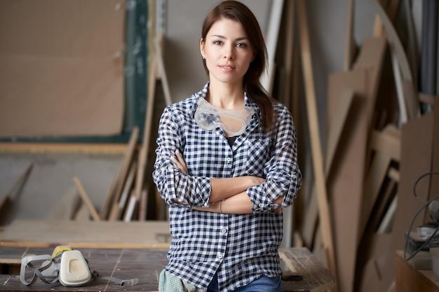 Vrouw timmerman met gekruiste armen in workshop