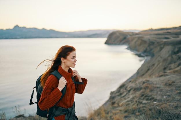 Vrouw toerist in een trui met een rugzak in de bergen in de buurt van het zijaanzicht van de zee