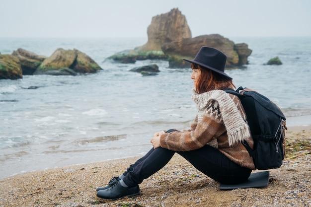 Vrouw toerist in hoed en met rugzak zittend op het strand kijkend naar zee aan de kustlijn aan de horizon