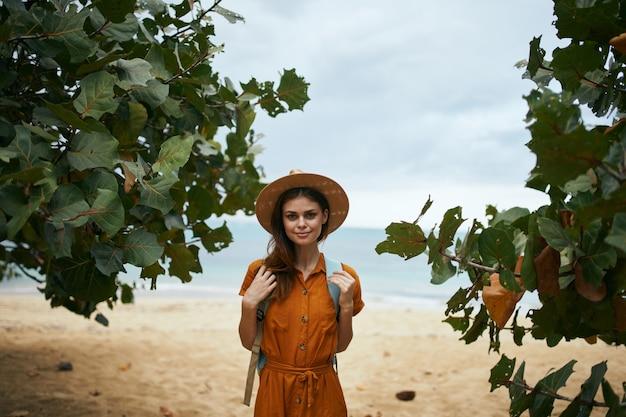 Vrouw toerist in hoed met rugzak op eiland landschap reizen