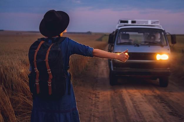 Vrouw toerist in hoed met rugzak stopt de auto op de weg in het midden van het veld