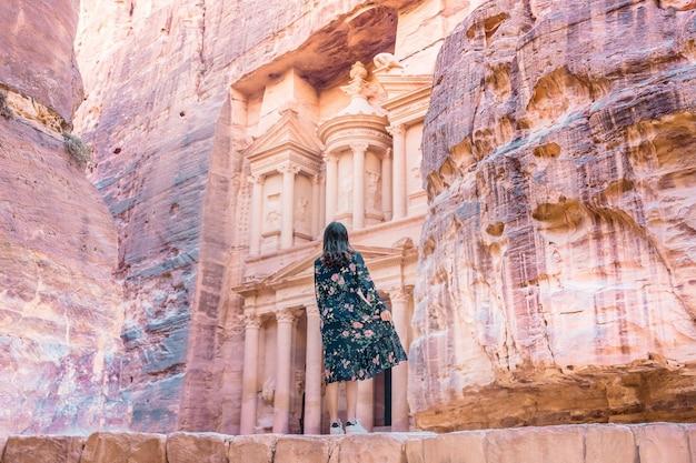Vrouw toerist in kleur jurk en hoed genieten van de schatkist, al khazneh in de oude stad van petra, jordanië