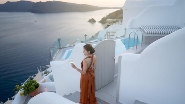 Vrouw toerist in prachtige jurk met glas wijn ontspannen bij zonsondergang
