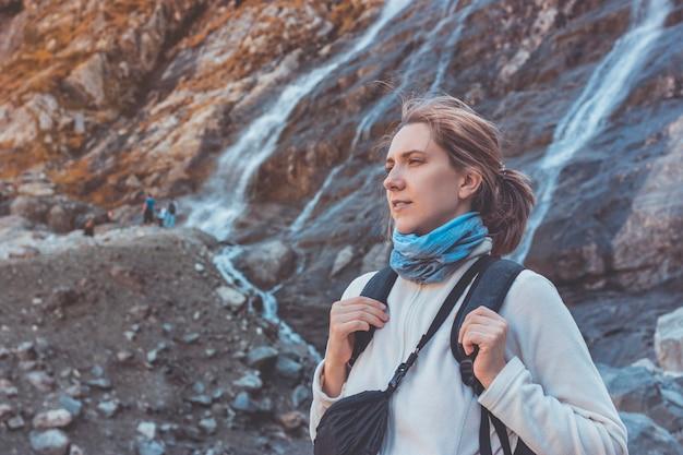 Vrouw toerist kijkt naar de bergen op een zonnige herfstdag. rusland, arkhyz.