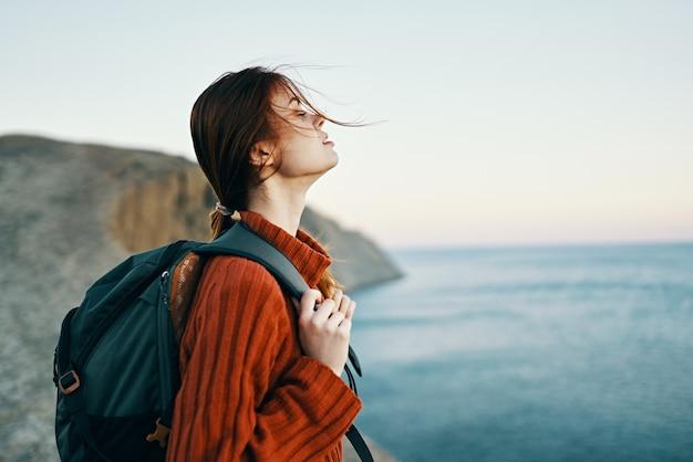 Vrouw toerist met een rugzak in een trui rusten in de bergen in de buurt van de zee en kijken