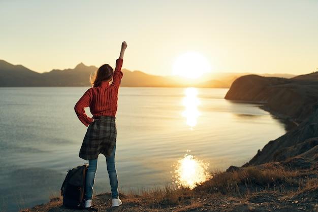 Vrouw toerist met opgeheven hand landschap zonsondergang vakantie