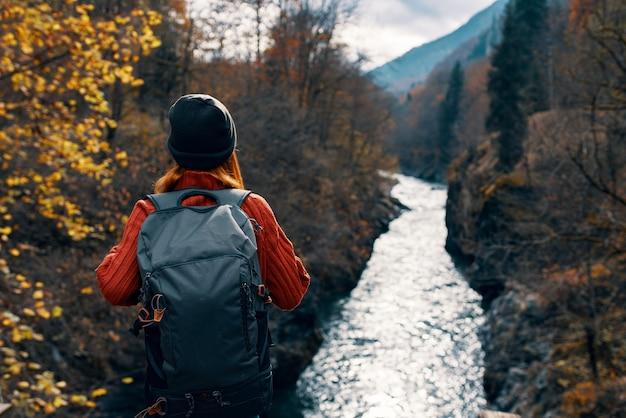 Vrouw toerist met rugzak bewondert natuur rivier bergen reizen