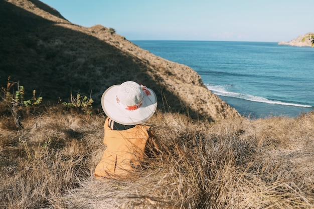 Vrouw toerist met zomerhoed zittend op de savanne met uitzicht op de zee en de heuvels