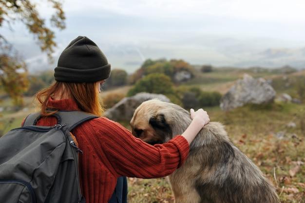 Vrouw toerist naast hond natuur reizen landschap dog
