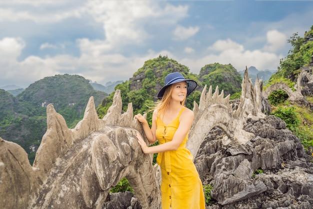 Vrouw toerist op achtergrond van verbazingwekkende enorme draak standbeeld op kalkstenen bergtop in de buurt van hang mua